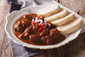 Nourishing goulash with boiled Knodel on a plate close-up. Horizontal