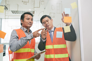 Experienced Asian engineer helping his coworker to draw a blueprint on glass wall