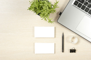 Business card blank, laptop, flower and pencil at office desk table top view. Corporate stationery branding mock-up