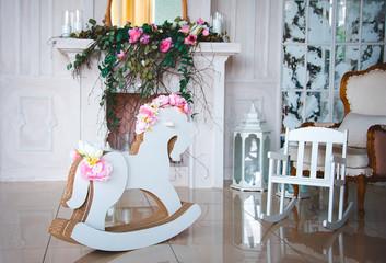 Детская лошадка и стульчик в красивом стильном интерьере.