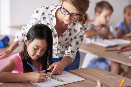 Teacher helping girl in homework