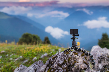 Action camera with selfie pole on the peak of mountain