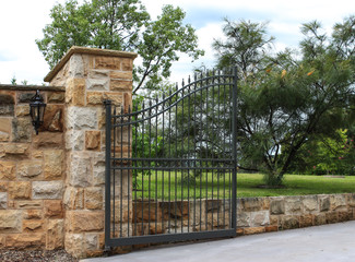 Wrought iron entrance gate set in sandstone bricks