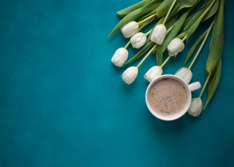 A cup of coffee and bouquet of white tulips. Top view.