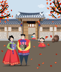 A couple dressed in Korean traditional costume and traditional Korean style house