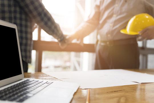 architect engineer shaking hands beside window - business teamwo