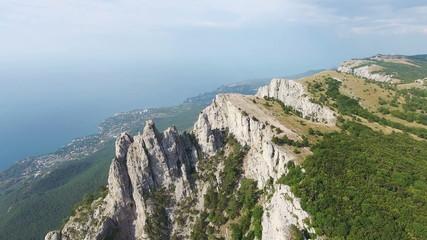 High rocks Ai-Petri of Crimean mountains. Black sea coast and blue sky with clouds