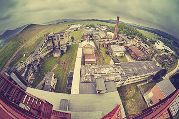 Vintage toned fisheye lens picture of an old abandoned coal mine in cloudy day.