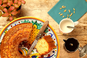 Breakfast with homemade ciambellone, milk, coffee. A plant, a blue napkin and some pine nuts.