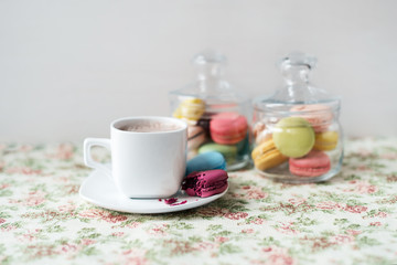 Crispy French macaroon and a cup of hot coffee on a vintage tablecloth.
