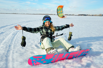 Beautiful girl is siting on the snow with kite on her legs on the background of snow and blue sky