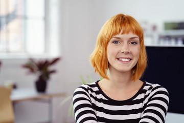 lächelnde frau in einem modernen büro am computer