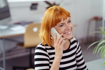 lächelnde frau telefoniert im büro