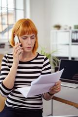 frau im büro schaut wütend auf einen brief und telefoniert