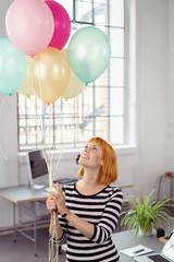 frau im büro mit luftballons