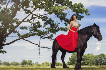 Beautiful woman with trendy make-up and in long red dress sitting on a black horse. Horse riding concept