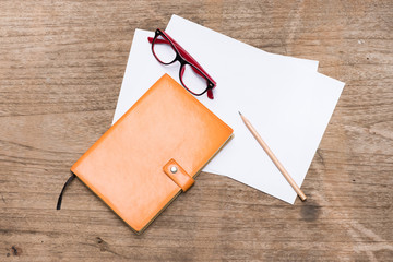 Top view orange diary,blank paper with pencil and eye glasses on wood table.