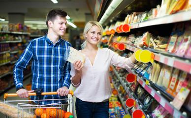 Couple choosing cheese at shop