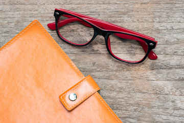 Diary booklet and eye glasses on wooden desk.