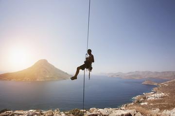 Rock climber against view of Telendos Island at sunset. Kalymnos Island, Greece