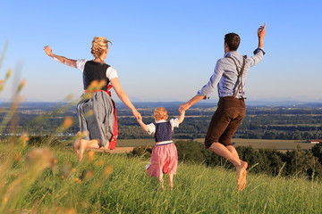 Familie in Tracht hüpft glücklich über Wiese