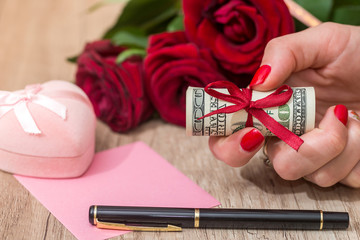 pink box, roses, money on the table