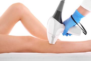 Depilacja laserowa nóg. Kobieta na zabiegu depilacji laserowej nóg