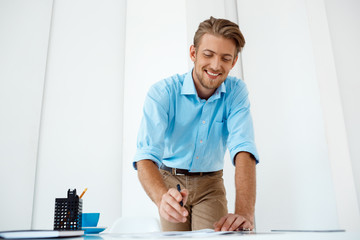 Young handsome confident cheerful smiling businessman working standing at table drawing sketch. White modern office interior background.