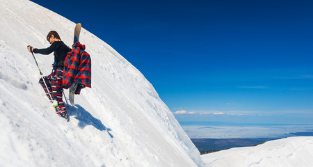 Young snowboarder climbing up the slope