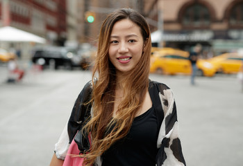 Young Asian woman in city walking smile happy face
