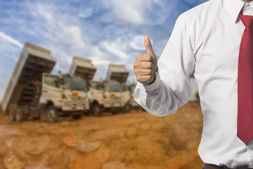 Businessman showing OK sign with his thumb up.on truck backgroun