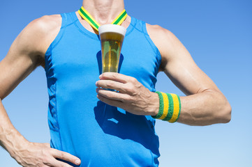 American athlete standing with first place gold medal in the shape of a glass of beer standing in front of blue sky