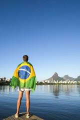 Athlete draped in Brazilian flag standing at Lagoa Rodrigo de Freitas lagoon with a view of Rio de Janeiro skyline with Two Brothers Mountain