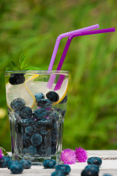 blueberry water with lemon on a wooden table.
