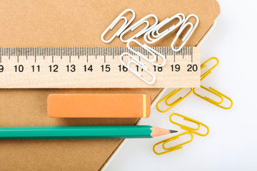 notebook, eraser, ruler, pencil and paperclips