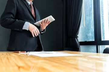 businessman in suit looking and tink vision of business with tablet