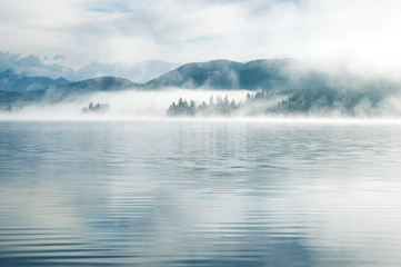Photo sur Aluminium Lac / Etang Heavy fog in the early morning on a mountain lake Early morning on Yazevoe lake in Altai mountains, Kazakhstan