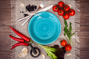 Fresh tomatoes, chili pepper and other spices and herbs around modern Turquoise plate in the center of wooden table and cloth napkin. Top view. Blank place for your text. Close-up.