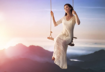 Fototapete - young woman on a swing
