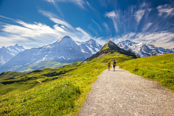 Fototapete - Young couple hiking in panorama trail leading to Kleine Scheidegg from Mannlichen with Eiger, Monch and Jungfrau mountain (Swiss Alps) in the background, Berner Oberland, Grindelwald, Switzerland.