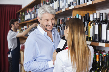 Customer Looking At Saleswoman Showing Wine Bottle
