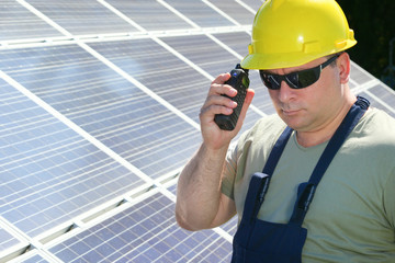 Engineer is make call with a  walkie talkie in solar power plant