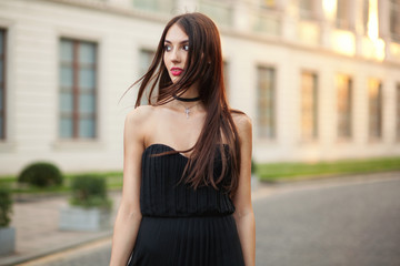 Fashion photo of beautiful elegant woman looking away at the str