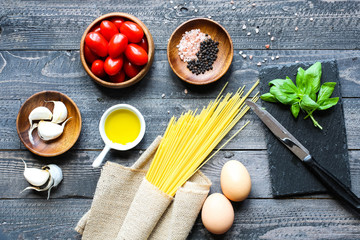 Top view of italian ingredients for tomato and basilic spaghetti with olive oil and garlic over a wood background.