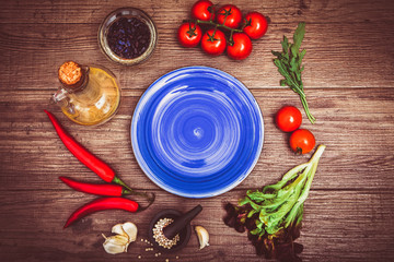 Fresh tomatoes, chili pepper and other spices and herbs around modern blue plate in the center of wooden table and cloth napkin. Top view. Blank place for your text. Close-up.