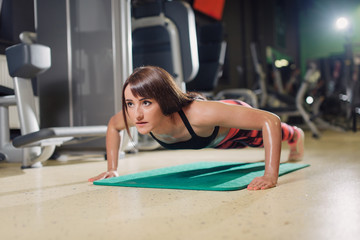 Young happy fit woman at the gym doing push-ups on a mat