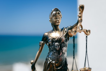 Justice Themis goddess sculpture on bright sky copy space background.