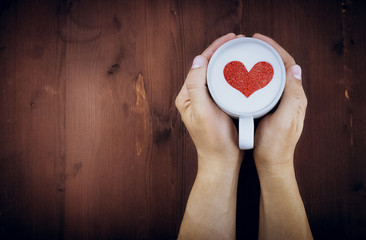 man holding hot cup of milk on wood table, with red heart shape, love concept