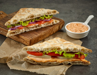 various sandwiches on paper and wooden cutting board