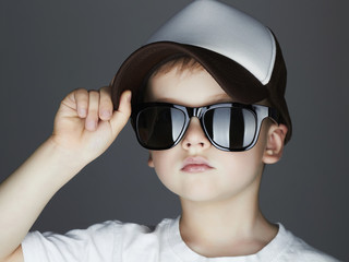 little boy in cap. fashion children.handsome in sunglasses and Tracker Hat